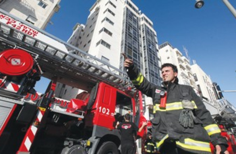 FIREFIGHTER stands outside an apartment building fire (photo credit: Marc Israel Sellem/The Jerusalem Post)