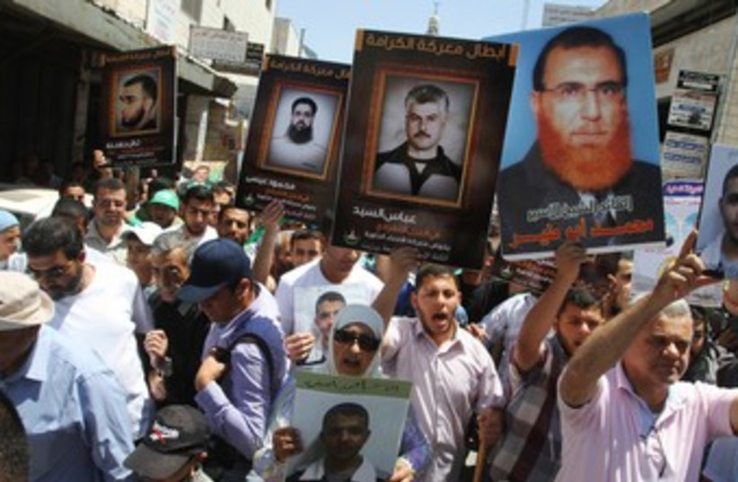 Palestinians in Ramallah hold pictures of prisoners 370 (R) (photo credit: REUTERS/Mohamad Torokman)
