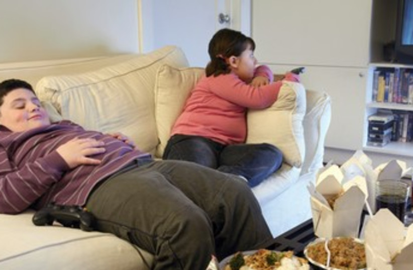 Overweight brother and sister sitting on a sofa (photo credit: Thinkstock/Imagebank)