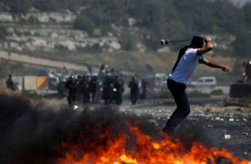 Palestinian throws stone at Beitunia Nakba Day protest 370 R (photo credit: REUTERS/Darren Whiteside)