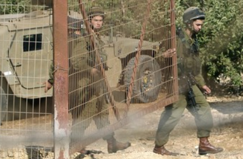 IDF soldiers close gate at Lebanon Border 370 (photo credit: Jamal Saidi / Reuters)