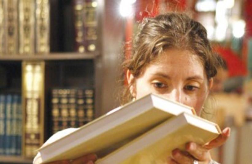 A woman searches through books 370 (photo credit: Ariel Jerozolimski)