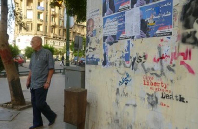 A man walks by a graffitied wall in DT Cairo 370 (photo credit: Eliezer Sherman)