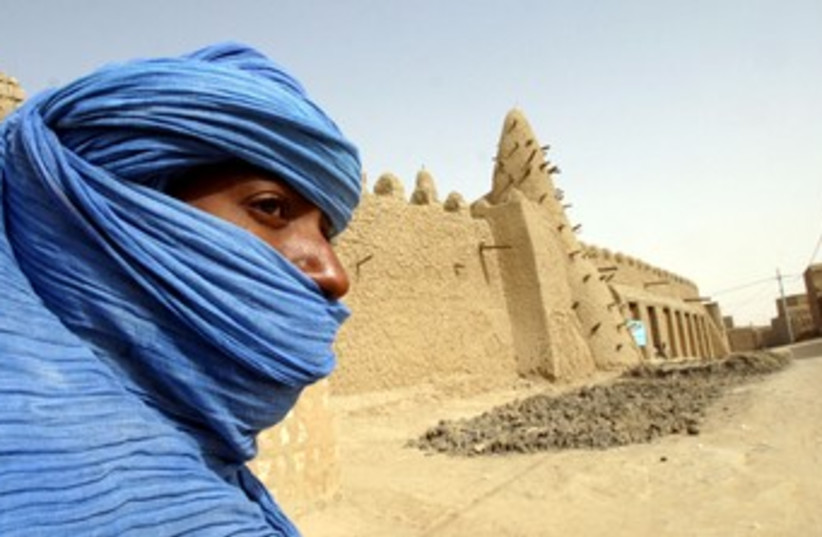 Tuareg nomad stands near 13th century mosque at Timbuktu 370 (photo credit: REUTERS)