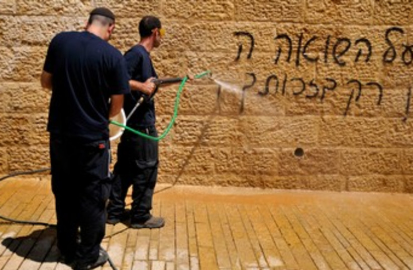 Workers cleaning graffiti at Yad Vashem 370 (photo credit: Hadas Parush)