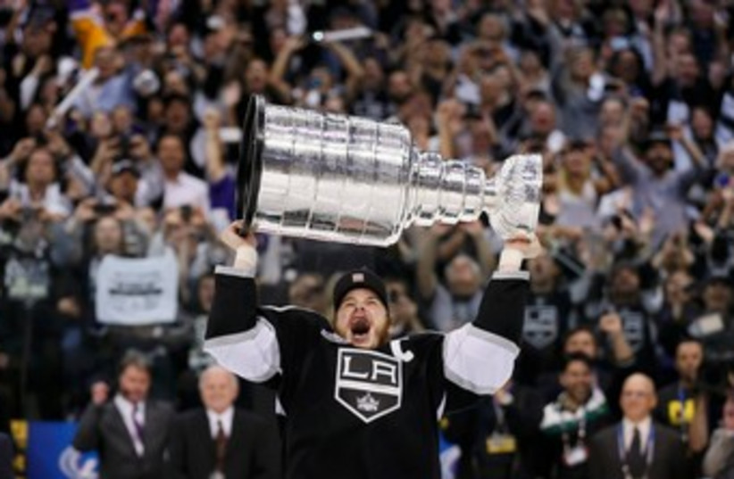 Kings right wing Dustin Brown hoists the Stanley Cup 370 (R) (photo credit: REUTERS/Lucy Nicholson)