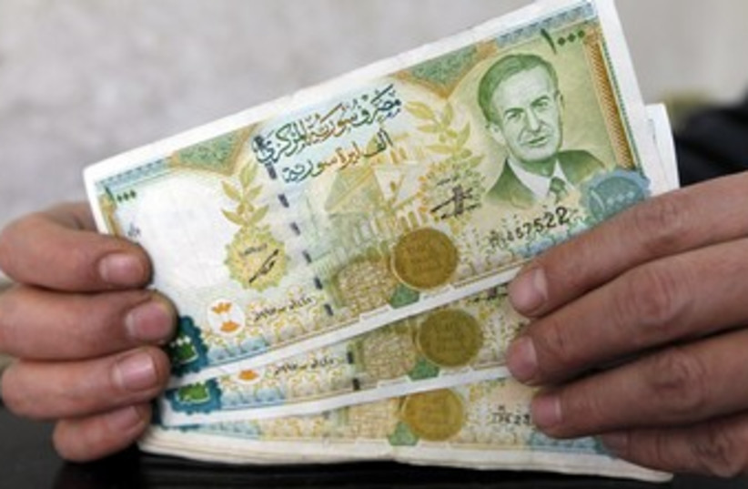 A money changer displays Syrian pounds 370 (R) (photo credit: Murad Sezer / Reuters)