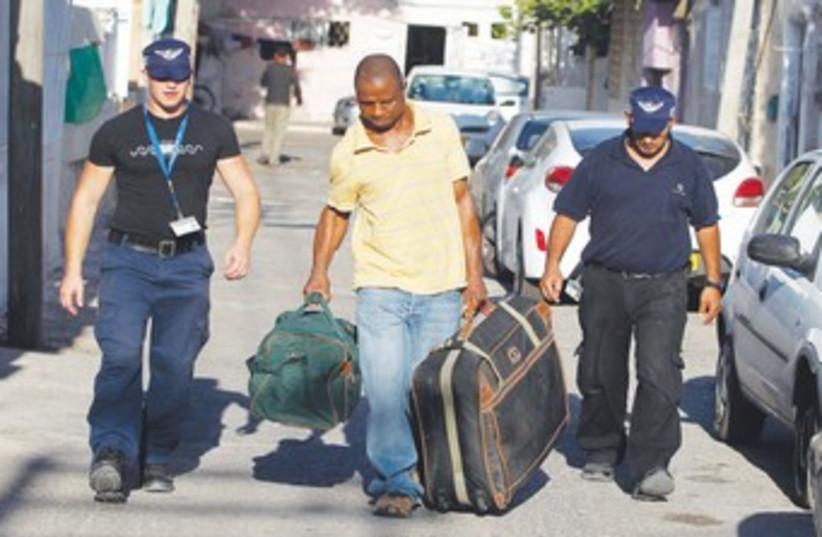 Immigration officers escort African migrant 370 (R) (photo credit: Baz Ratner/Reuters)