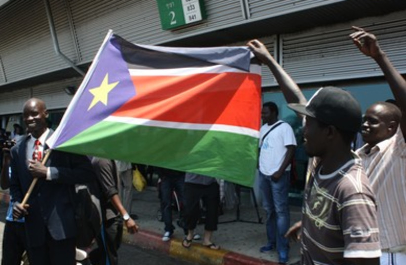 Migrants dance with flag of South Sudan (photo credit: Ben Hartman)