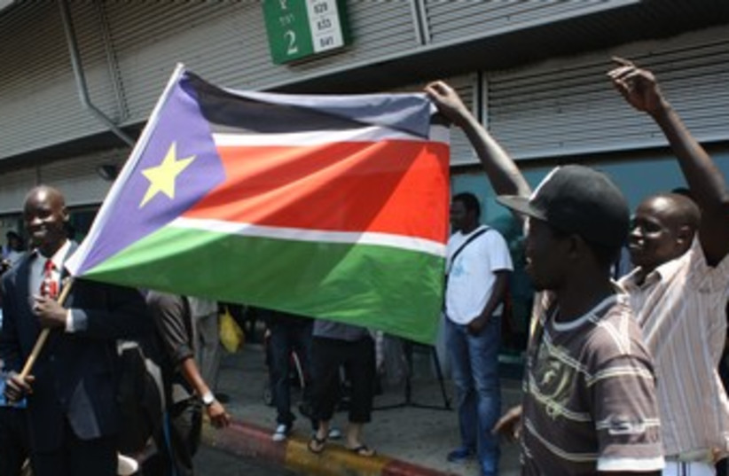 Migrants dance with South Sudanese flag 370 (photo credit: Ben Hartman)