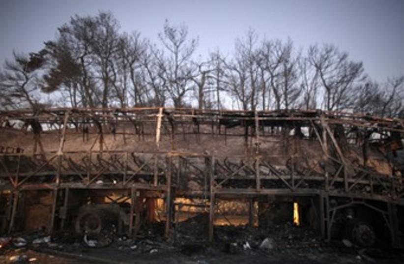 Burned out Prison Service bus from Carmel Fire 370 (R) (photo credit: NIR ELIAS / Reuters)
