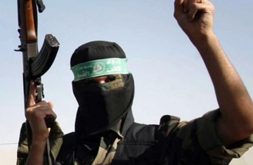 A masked Hamas man holds a gun 370 (R) (photo credit: Ibraheem Abu Mustafa / Reuters)