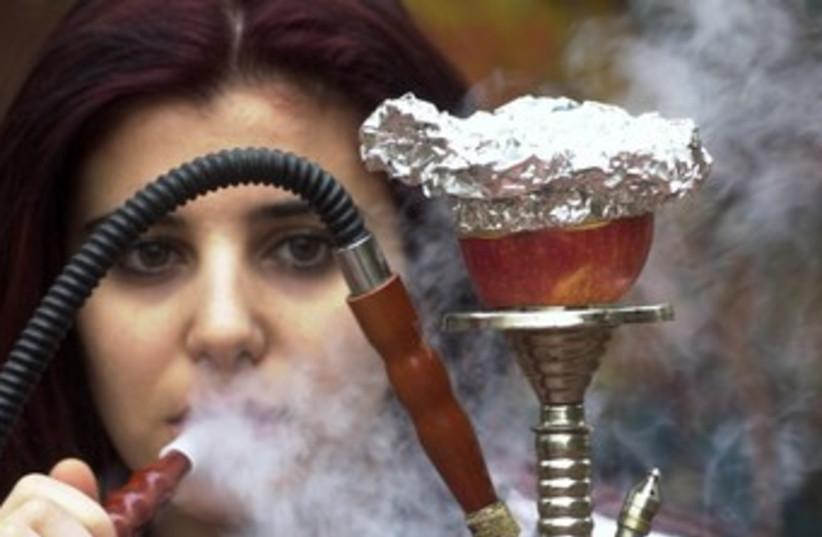 Woman smokes nargila from a hookah 370 (photo credit: REUTERS/Sharif Karim)
