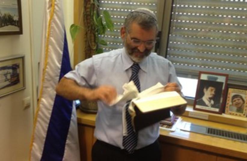 MK Ben-Ari tearing up a New Testament 370 (photo credit: Itamar Ben-Gvir)