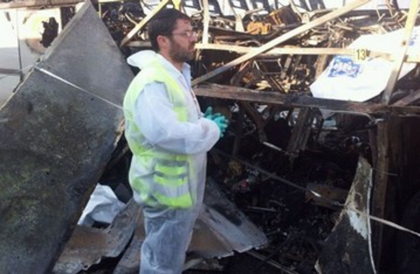 ZAKA man examines damage in Burgas 390 (photo credit: Avigdor Shatran)