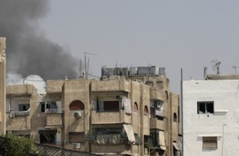 Smoke is seen rising over Damascus 370 (R) (photo credit: REUTERS)