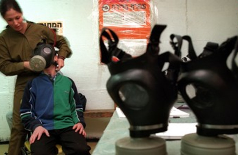IDF soldier fits child with gas mask 370 (photo credit:   REUTERS/David Silverman)