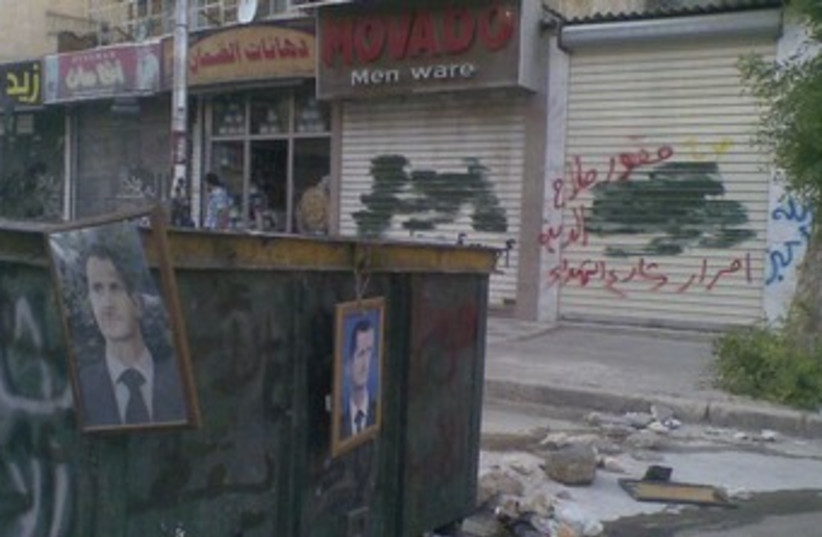 Pictures of Assad hang from garbage containers in Aleppo 370 (photo credit: REUTERS)