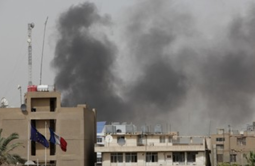 Smoke rises from the site of a bomb attack in Baghdad 370 (photo credit: REUTERS)
