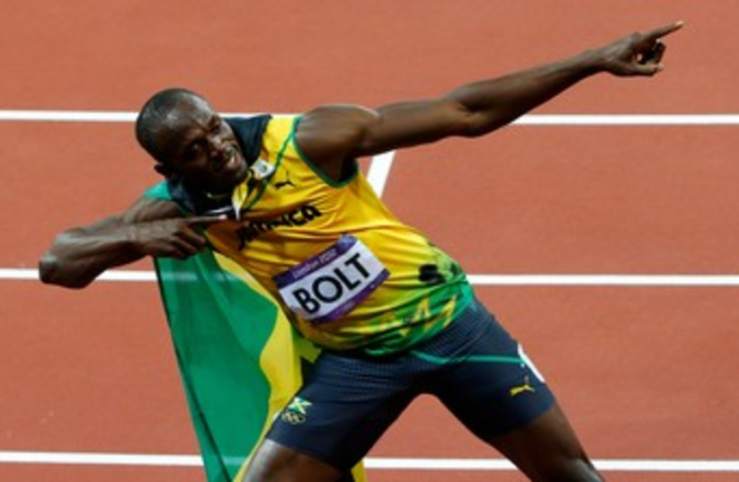 Usain Bolt after winning the 100m 370 (R) (photo credit: REUTERS)