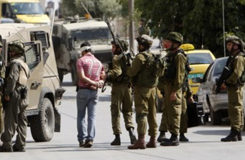 IDF soldiers arrest a Palestinian in Ramallah 370 (R) (photo credit: Mohamad Torokman / Reuters)