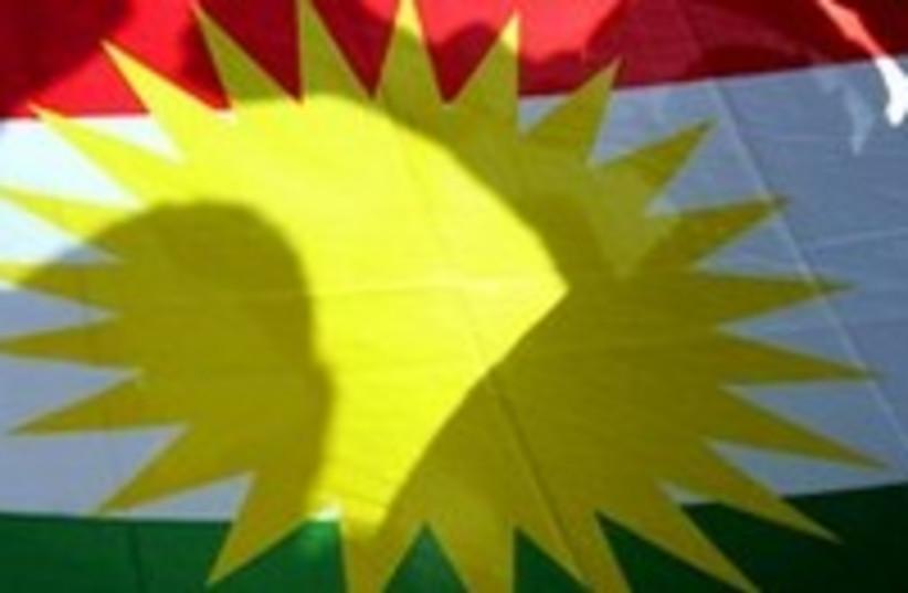 Kurds pose behind Kurdish flag_300 (photo credit: Mike Finn-Kelcey/Reuters)