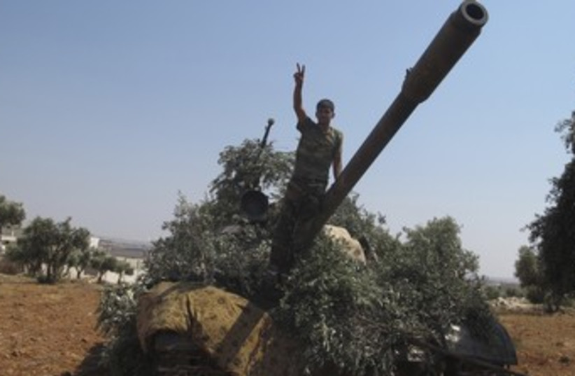 Syrian rebel with captured tank 370 (photo credit: REUTERS)