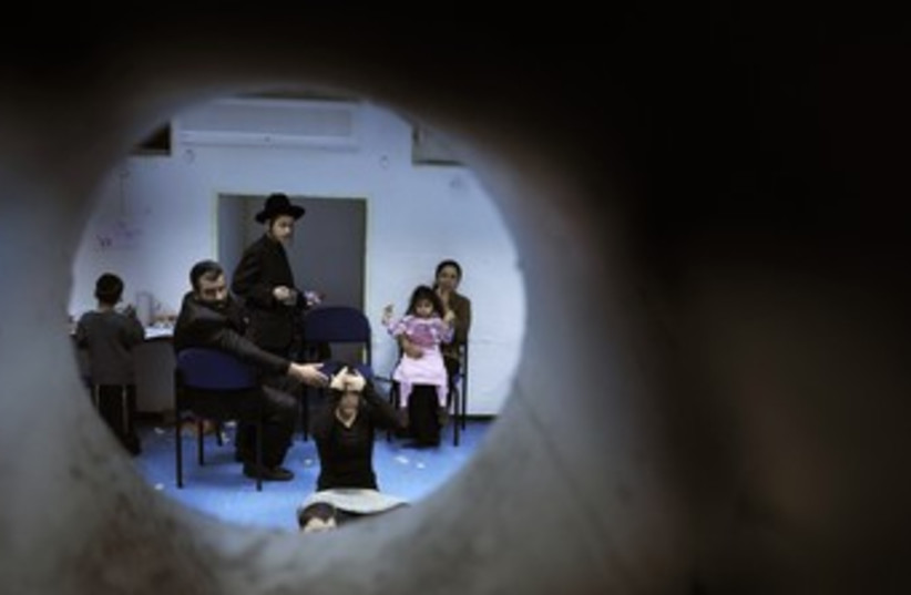 Israelis in Bomb Shelter (photo credit: Amir Cohen / Reuters)