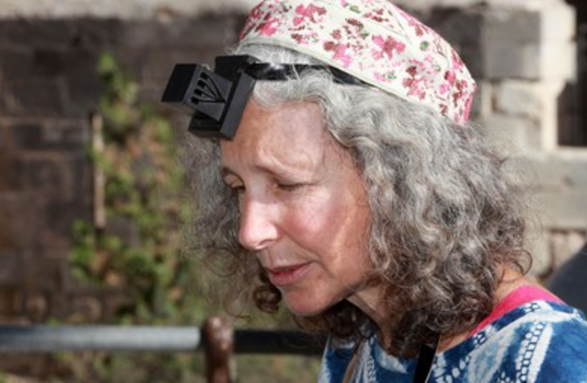 Woman puts on Tefillin