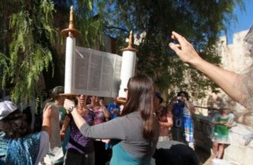 Woman raises Torah scroll 370 (photo credit: Marc Israel Sellem /The Jerusalem Post)