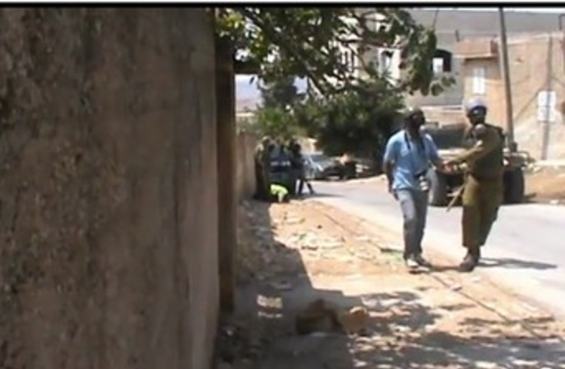 IDF soldier with baton with Palestinian (photo credit: YouTube Screenshot)