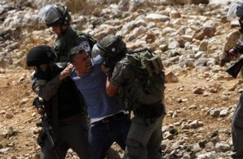 Security forces detain a Palestinian in Nabi Saleh 370 (R) (photo credit: Mohamad Torokman / Reuters)
