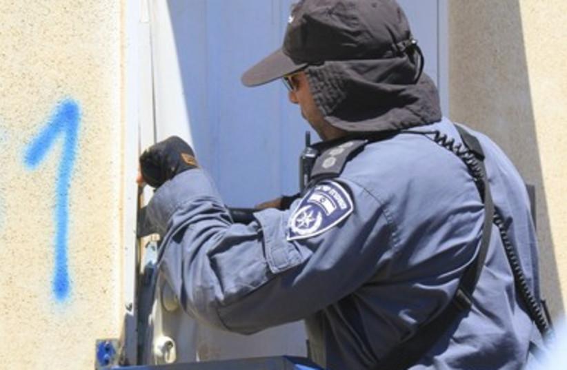 Border police uses crow bar to break open the door
