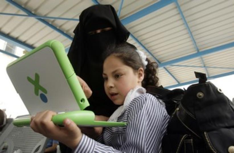 Gaza teacher shows a girl how to use computer 370 (R) (photo credit: Ibraheem Abu Mustafa / Reuters)