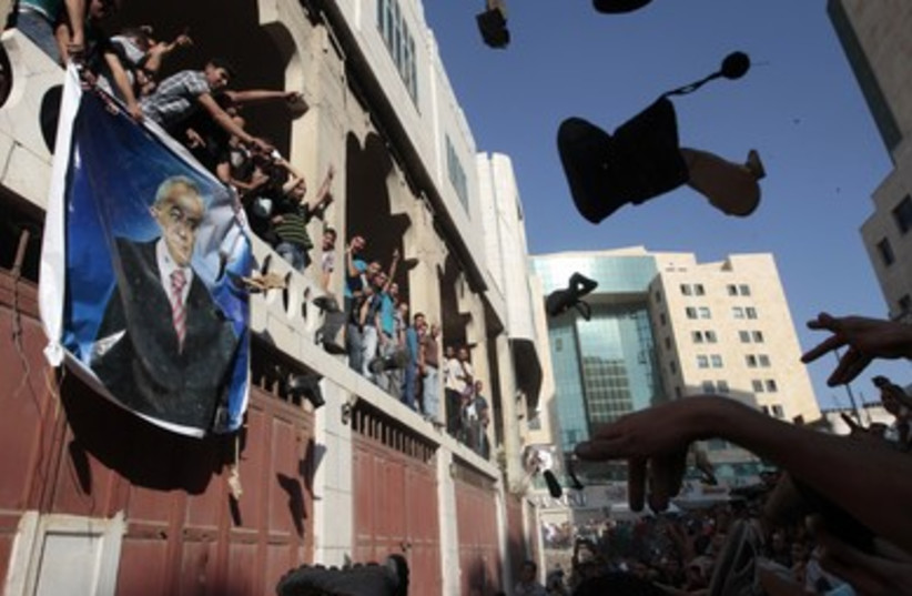 protesters throw shoes at a banner of PM Fayyad