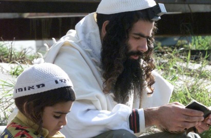 ORTHODOX JEW PILGRIM READS IN UMAN 521 (photo credit: REUTERS/Gleb Garanich)