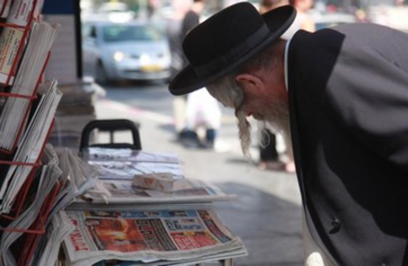 Orthodox haredi man reads newspapers media news 390 (photo credit: Marc Israel Sellem / The Jerusalem Post)