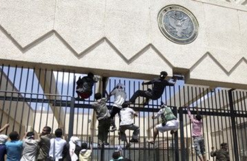 Protesters climb a fence at US embassy in Sanaa