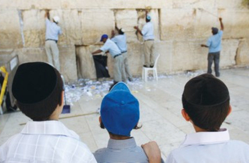 Boys watch notes removed from kotel 390 (photo credit: Ronen Zvulun/Reuters)
