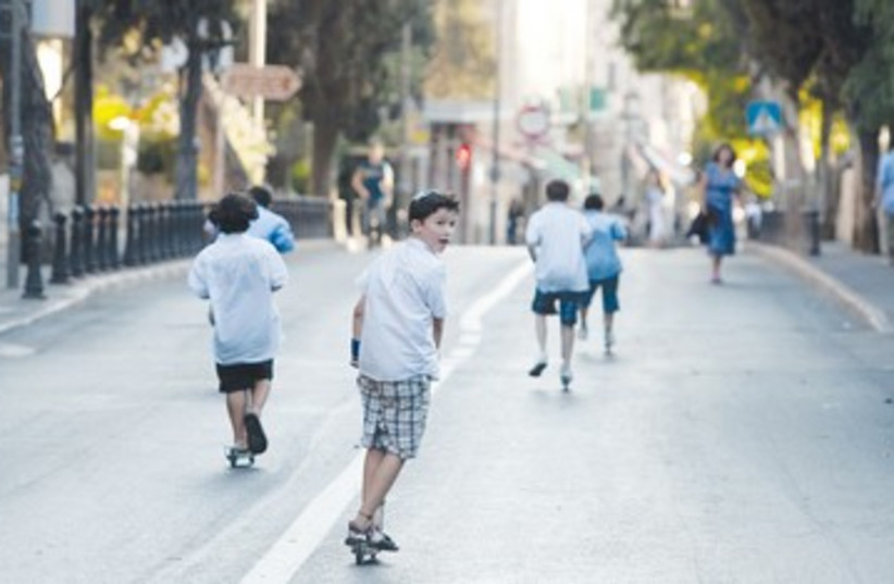 Kids ride scooters on Yom Kippur 390 (photo credit: Darren Whiteside/Reuters)