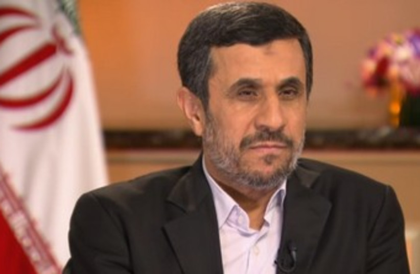 Ahmadinepoopoo with flag behind him 370 (photo credit: Screenshot)
