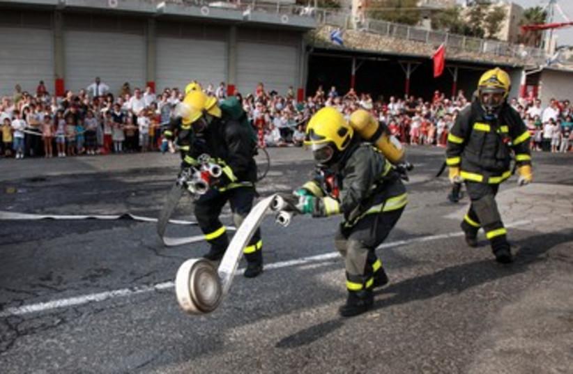 Firefighters unravel hose (photo credit: Marc Israel Sellem)