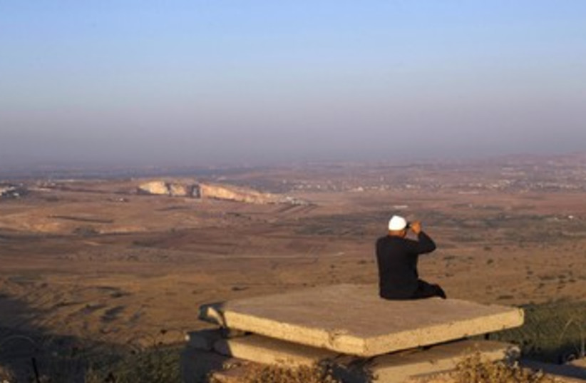 Druse man looks out at Syria from the Golan 370 (R) (photo credit: Ronen Zvulun / Reuters)