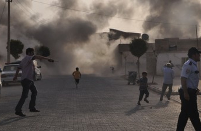 Smoke rises after mortar bomb lands in Turkish village 370 (photo credit: REUTERS)