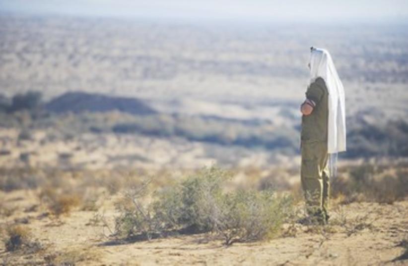 A haredi soldier prays during a drill (photo credit: IDF Spokesman))