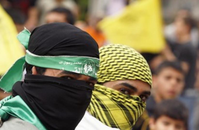 Palestinians wearing Hamas, Fatah masks 370 (photo credit: REUTERS/Ismail Zaydah)
