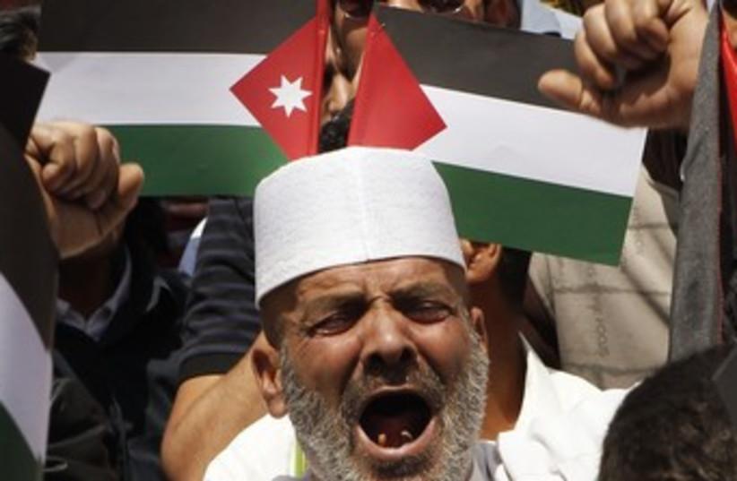 Man yelling in front of Palestinian, Jordanian flags 370 (photo credit: REUTERS/Ali Jarekji)