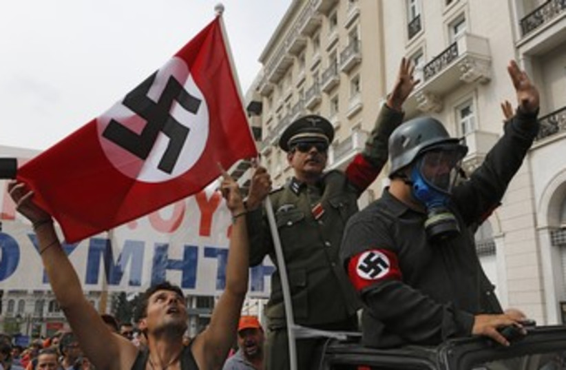 Greeks wave swastikas to greet Merkel 370 (photo credit: REUTERS/Yannis Behrakis)
