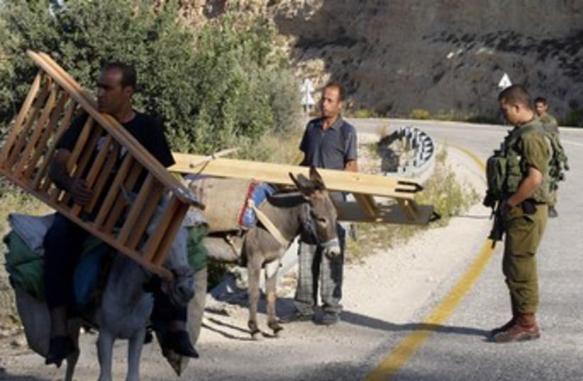 Palestinians return from olive harvest, idf guards 370 (photo credit: Reuters/Abed Omar Qusini)