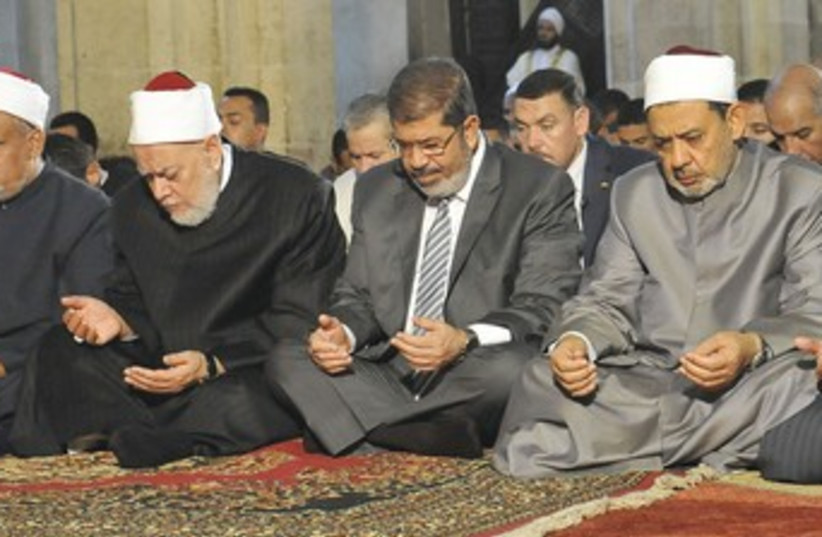 MOHAMED MORSI, center, prays at Al-Azhar mosque in Cairo 370 (photo credit: REUTERS)
